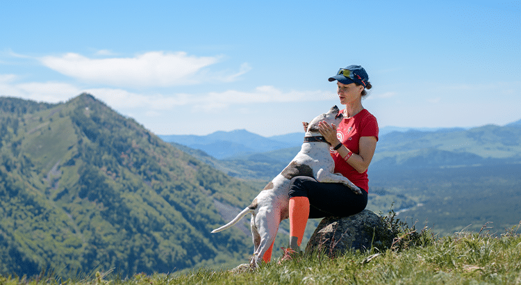 Athletic woman and a dog bonding on top of a mountain